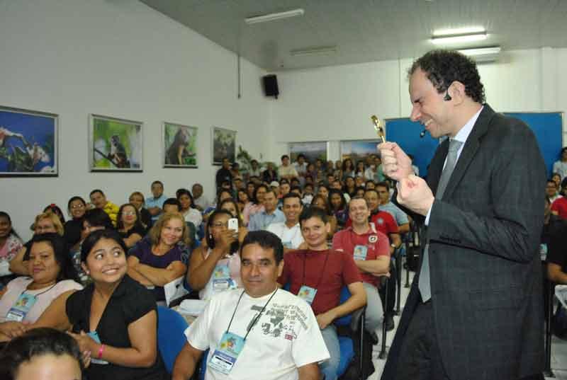 Com uma lupa o palestrante Daniel Bizon interage com público