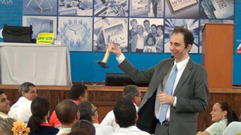 Palestrante Daniel Bizon fazendo humor com um martelo na mão