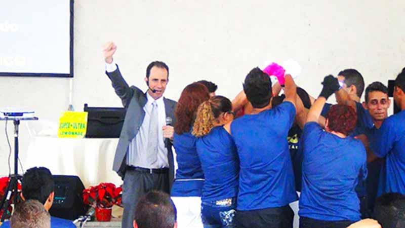Daniel Bizon e um grupo de pessoas no palco comemorando
