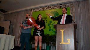 Daniel Bizon e dois estudantes sendo homenageados no palco